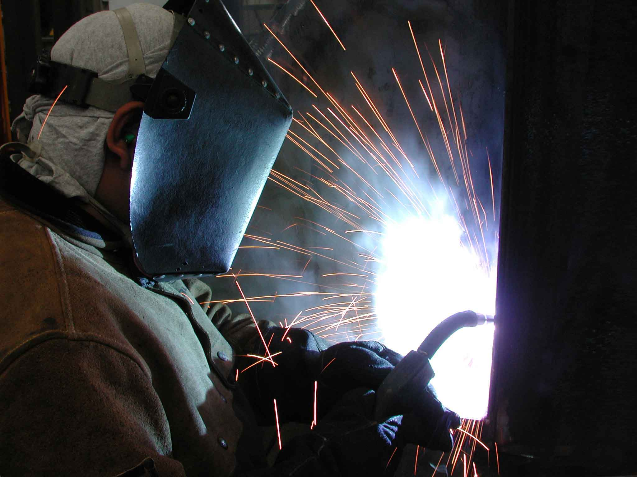 Welder in welding shop wearing a mask and welding on a piece of metal.