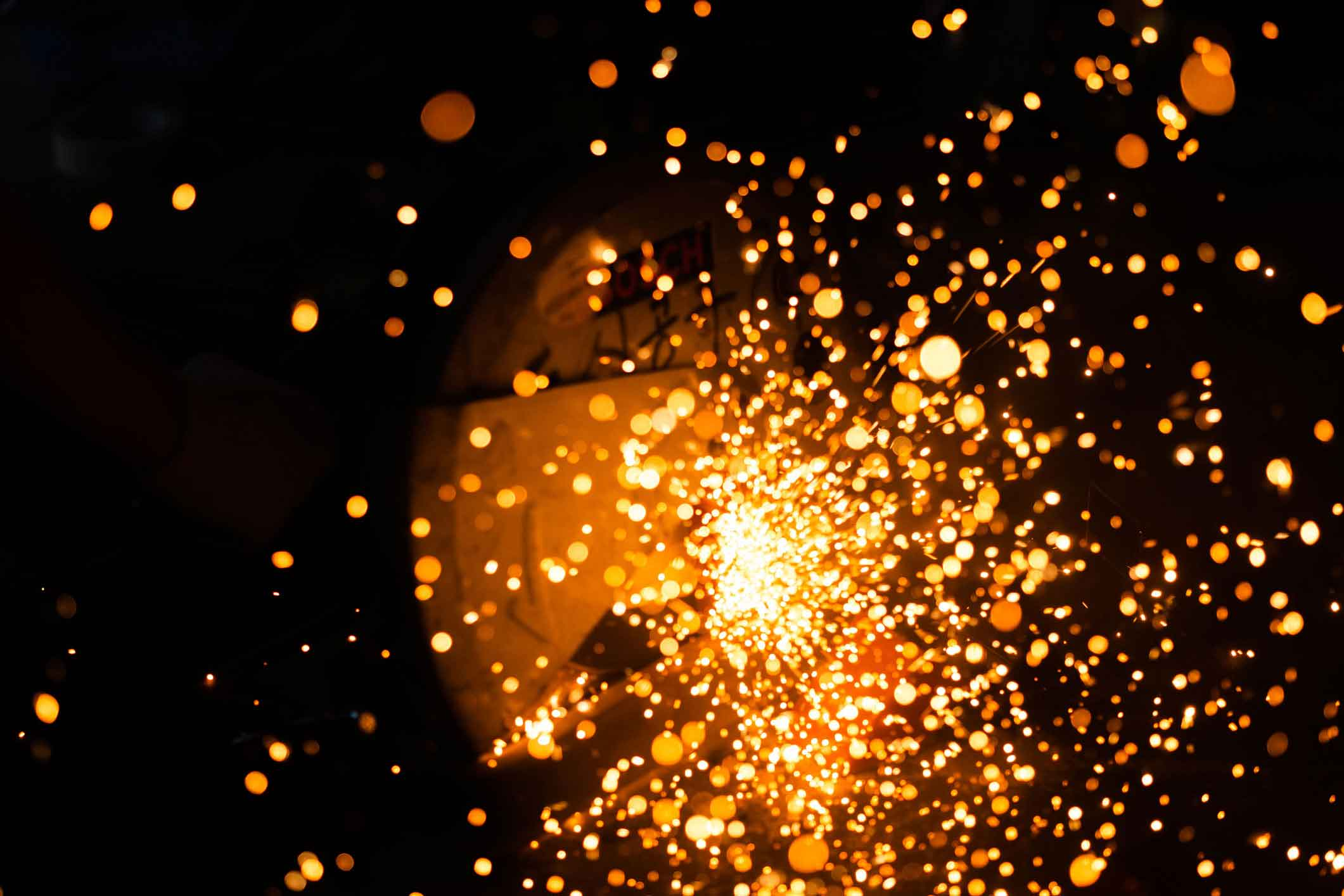 Orange sparks from welding shop or machine shop representing welding pollutants.