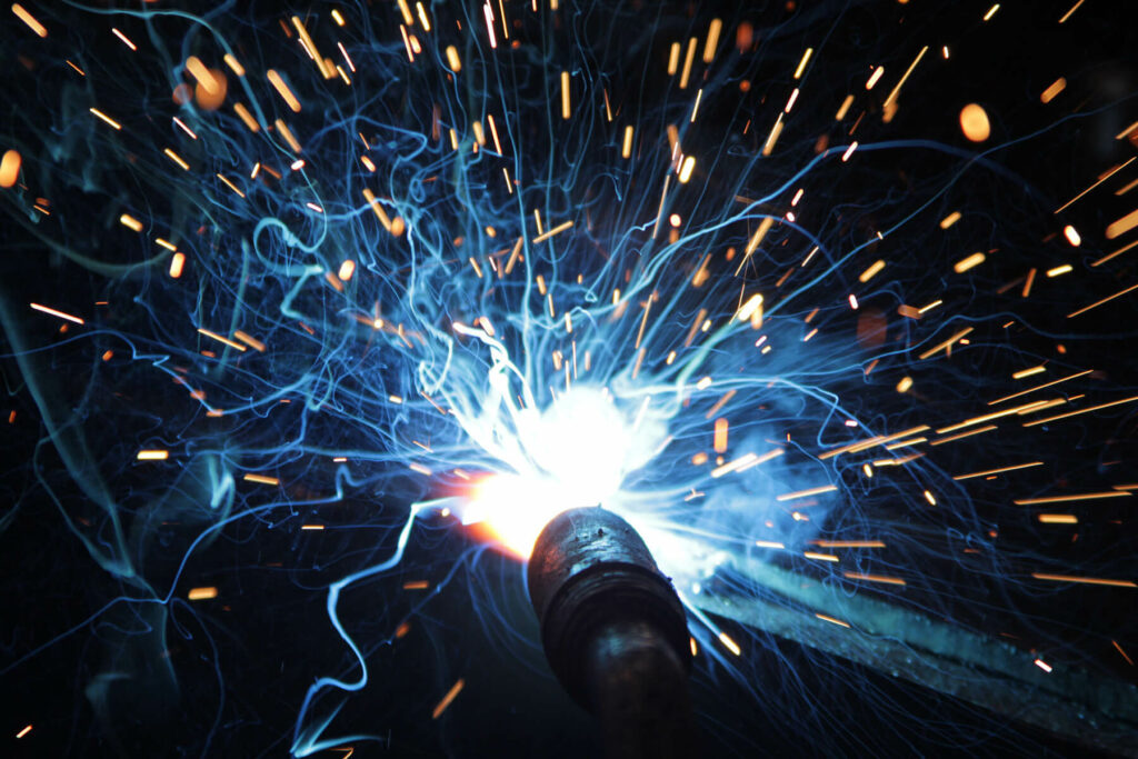 Welding flashes and sparks representing the need for air filtration in welding shops and machine shops.